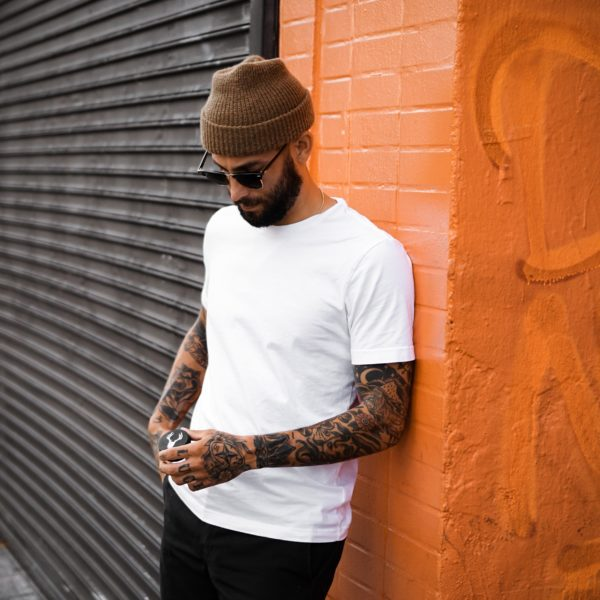 man in white crew neck t-shirt and black pants standing beside black wall