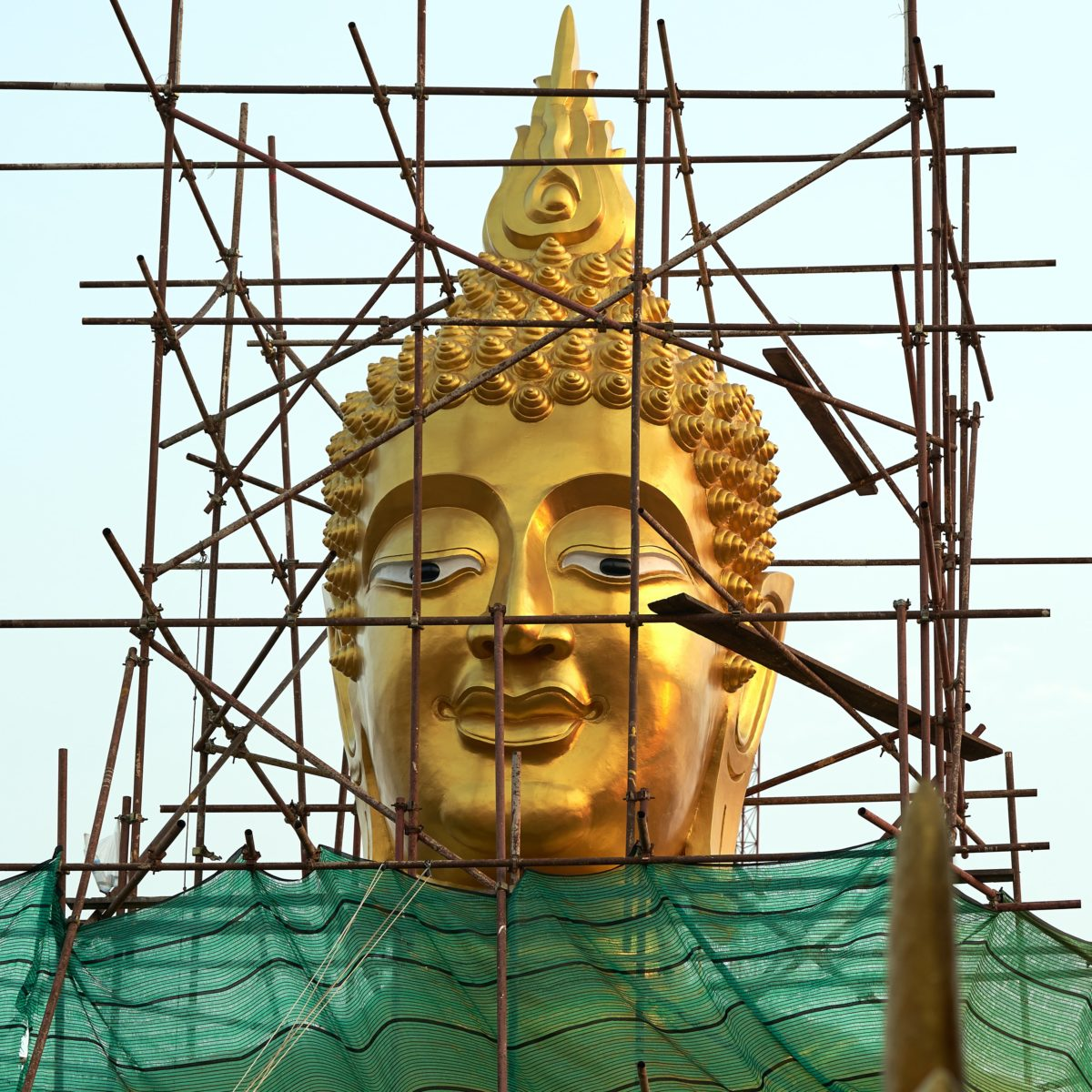 gold buddha statue on green textile